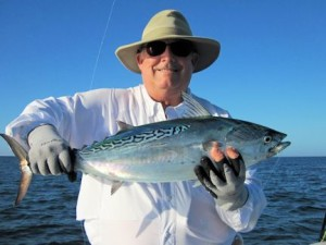 Lynn Skipper, from Apollo Beach, FL, with a false albacore (little tunny) caught and released on a fly while fishing with Capt. Rick Grassett in a previous December.
