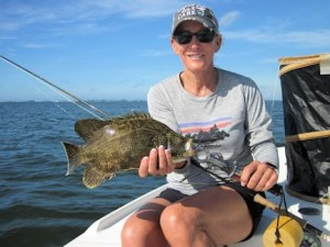 Sunny Moss, from Sarasota, with a tripletail caught and released on a fly on her first fly fishing trip while fishing in Sarasota with Capt. Rick Grassett